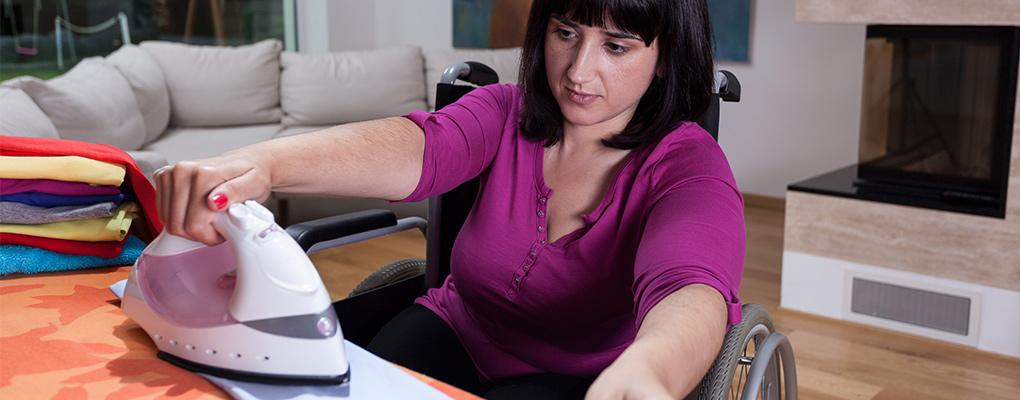 Woman in wheelchair ironing