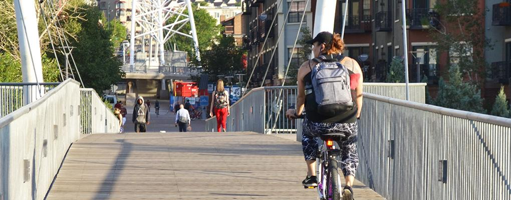 Cyclists and pedestrians crossing pedestrian bridge toward downtown Denver