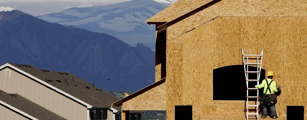 Construction worker building a new home with mountains in the background.